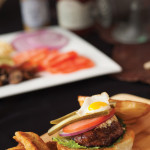 A Black Angus chipotle bison burger with lettuce, tomato, pickles, onion, cheese and a fried quail egg, with deep fried pickles on the side.