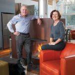 Architects Peter Ortved and Maureen O'Shaughnessy with dog Marley in front of the two-sided fireplace in their sitting area. The fireplace, from Belgium, has a pre-rusted finish of corten steel.