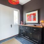 Doors in the breezeway open to a mudroom. Slate flooring is a practical choice in the mudroom entrance. The drum light pendant by Foscanini is from Lumens. Art by Lila Lewis Irving. Sisal carpet from Mackenzie-Childs.