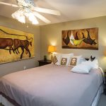 One of several guest rooms used for visiting family and friends features a cow painting found in a nearby barn and cleaned up. Resting on the bed is Morrissey's rescue dog, Odie.