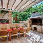 A pergola with a canvas shade covers an outdoor kitchen.