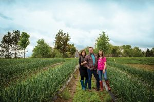 Kimberly and Tim Schneider and daughter Teaghen among the garlic crop at Dunridge Farms.