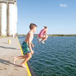 Claire and Reed Johnson jump off the Collingwood pier beside the grain terminal.