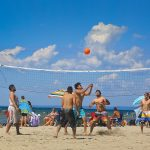 Beach volleyball players enjoy a game at Wasaga Beach while other beachgoers of all ages partake in a variety of activities on sand and water.