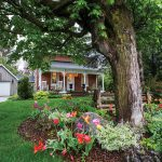 An old-fashioned veranda on the century home looks over the shaded front yard.
