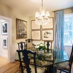 In the dining room, raw silk curtains add a layer of softness and balance the walls filled with art.