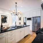 The renovated kitchen was kept simple and classic with black quartz countertops, white Shaker-style cabinetry and plenty of white walls for framed photography.