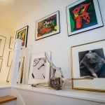 A whalebone Inuit sculpture bought at Huston Gallery North in Lunenburg, Nova Scotia rests on the stair landing between two of the owner's collection of art and fashion photographs. The prints above the sculpture are by Karel Appel.