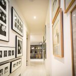 White walls and floors in the upstairs hallway provide a clean backdrop for framed photographs.