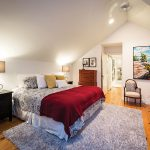 The master bedroom was enlarged and redesigned during the renovation. A landscape by Ryan Allen Sobkovich occupies one wall.